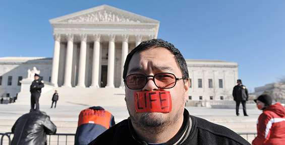 Man protesting abortion stands in front of the US Supreme Court with tape over his mouth. Photo by Carl E. Feather